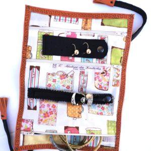 trousse à bijoux cuir orange, intérieur blanc imprimé de valises